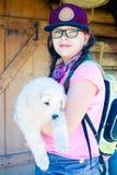 户外拿着一只大小狗的年轻远足者女孩 库存图片