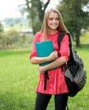 户外拿着笔记本的女性微笑的学员 免版税库存图片