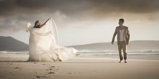 户外挥动在海滩的年轻浪漫新娘夫妇 库存照片
