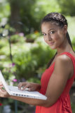 户外摆在妇女年轻人的膝上型计算机 库存图片