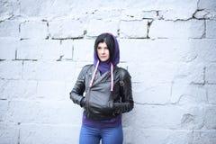 户外摆在黑皮革的美丽的年轻深色的妇女 库存图片
