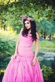 户外时尚在绿叶开花的树的女孩画象 免版税库存照片