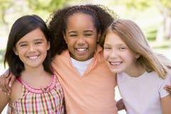 户外朋友女孩三个年轻人 免版税库存图片