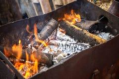 户外木柴的燃烧 木柴为烹调烤肉做准备 在格栅的油炸物肉 木头背景 免版税库存照片
