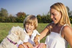 户外母亲、儿子和逗人喜爱的狗 免版税图库摄影