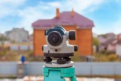 户外测量员设备光学水平或经纬仪在建造场所在大厦指挥了 免版税库存照片
