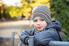 户外温暖的衣裳的美丽的小男孩 图库摄影