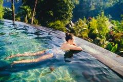 户外游泳池的美丽的妇女 与晒日光浴在无限游泳池的妇女的假日概念 免版税库存照片