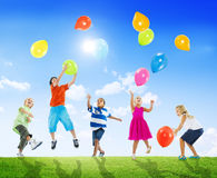 户外演奏气球的不同种族的孩子 库存照片