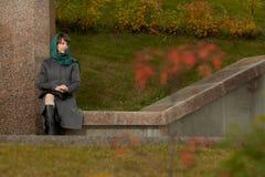 户外灰色外套的美丽的时髦的妇女 图库摄影