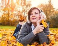 户外灰色毛线衣的快乐的美丽的妇女在美好的秋天天 免版税库存照片