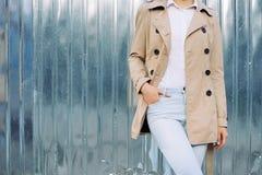 户外牛仔裤、一件米黄外套和白色衬衣的亭亭玉立的女孩在春天 免版税库存图片