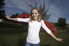 户外瓢虫服装的女孩 免版税图库摄影