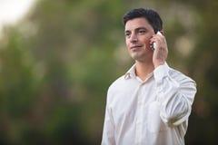 户外电话的年轻人 免版税库存照片