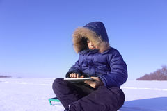 户外男孩与片剂个人计算机在冬天 免版税库存图片