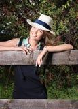 户外画象 站立在木篱芭的轻的帽子的年轻美丽的妇女 图库摄影