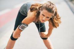 户外疲乏的健身妇女在城市 免版税库存图片
