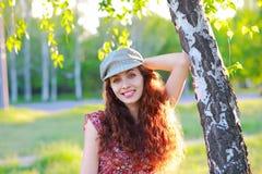 户外盖帽的秀丽女孩 免版税图库摄影