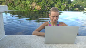 户外相当比基尼泳装的白肤金发的愉快的妇女画象有在屋顶无限游泳池的便携式计算机的 股票录像