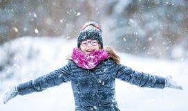 户外秀丽冬天愉快的女孩吹的雪在冷淡的冬天公园或 女孩和冬天冷气候 免版税图库摄影