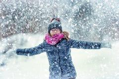 户外秀丽冬天愉快的女孩吹的雪在冷淡的冬天公园或 女孩和冬天冷气候 免版税库存图片