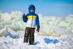 户外站立在冬天海滩的逗人喜爱的小男孩 免版税库存照片