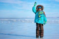 户外站立在冻海的逗人喜爱的小男孩 免版税图库摄影