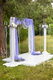 户外紫色婚礼装饰,枝形吊灯,登记在森林里 免版税库存图片