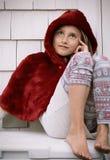 户外红色海角的女孩 免版税库存照片