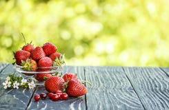 户外红色草莓在一张老桌上 库存图片
