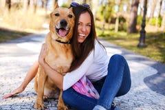 户外美丽的女孩生活方式画象有一条逗人喜爱的狗的si 图库摄影
