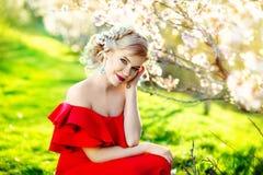 户外美丽的女孩画象摆在夏天庭院里的豪华红色礼服的 库存图片