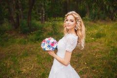 户外美丽的新娘在森林里 免版税库存图片