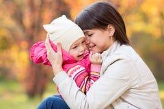 户外美丽的母亲和孩子女孩在秋天同水准 免版税图库摄影