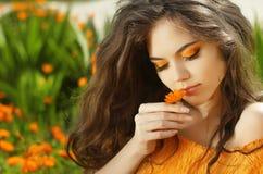 户外美丽的青少年的女孩嗅到的花画象,在m 图库摄影