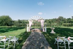 户外美好的夏天婚礼 在草的装饰的椅子立场 婚礼曲拱由轻的布料制成和白色和pi 免版税库存照片
