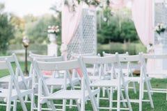 户外美好的夏天婚礼 在草的装饰的椅子立场 婚礼曲拱由轻的布料制成和白色和pi 库存照片