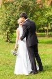 户外美好的婚礼夫妇 他们亲吻并且互相拥抱 库存图片