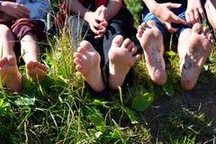 户外腿的儿童的赤裸脚 孩子坐草和展示腿 图库摄影