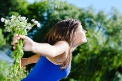 户外自由:享受太阳愉快微笑的光芒&拿着雏菊的花束美丽的少妇画象  免版税图库摄影