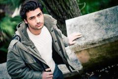 户外英俊的年轻意大利人、时髦的头发和外套 免版税图库摄影