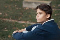 户外英俊,沉思和严肃的青少年的男孩画象  人 库存图片