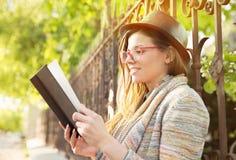 户外读妇女年轻人的书 免版税图库摄影