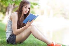 户外读妇女年轻人的书 图库摄影
