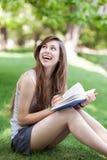 户外读妇女年轻人的书 免版税库存图片