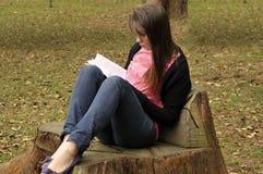 户外读妇女的书 免版税库存图片