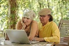 户外资深夫妇与膝上型计算机 库存照片
