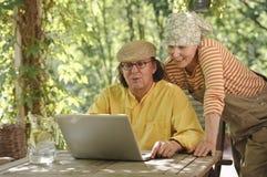 户外资深夫妇与膝上型计算机 库存图片