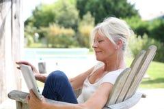 户外资深妇女阅读书画象  免版税图库摄影