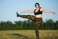 户外超重肥胖妇女训练腿 解决在开放ai 免版税库存照片